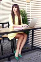 Geschäftsfrau, die am Schreibtisch arbeitet, der auf einem Laptop tippt