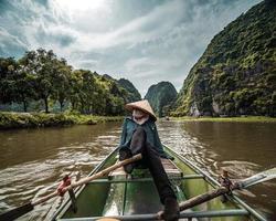 Person im konischen Hut im Boot am Fluss