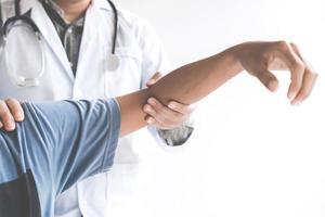 Arzt, der den Ellbogen des Patienten überprüft foto