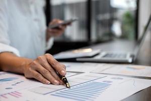 Unternehmer am Schreibtisch Berechnung der Kosten foto