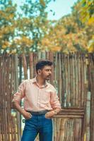Mann posiert vor Holztor