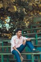 junger Mann sitzt auf Bank foto