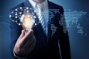 Geschäftsmann, der Glühbirne mit Karte der Welt hält