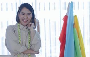 Frau Modedesignerin lächelt in der Nähe von Kleidung