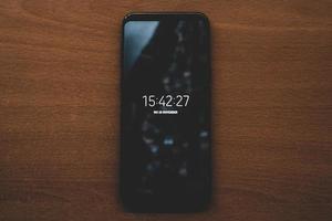Draufsicht des Telefonbildschirms auf Holztisch foto