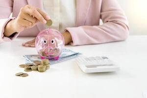 Geschäftsfrau, die Münzen in Sparschwein legt foto