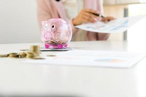 Geschäftsfrau, die Dokumente mit Sparschwein prüft foto