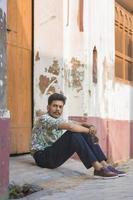 junger Mann sitzt im Türrahmen foto