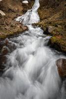 Wasserfall den grasbewachsenen Berghang hinunter