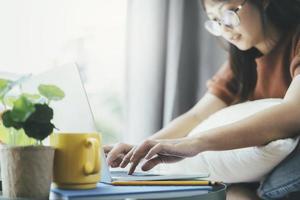 Frau, die zu Hause auf Laptop schreibt foto