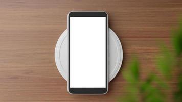 Draufsicht auf ein Smartphone auf einem Ladegerät foto