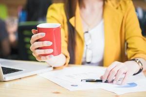 Nahaufnahme der Geschäftsfrau, die eine Kaffeetasse hält foto