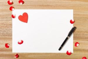 Draufsicht auf Papier mit einem Stift und roten Blütenblättern foto