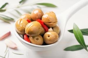 Nahaufnahme von gewürzten Oliven im Löffel