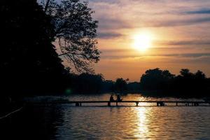 Menschen genießen Sonnenuntergang am See foto