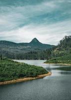 grüne Hügel in der Nähe eines Sees foto
