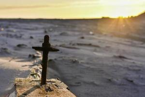 Kreuz am Strand bei Sonnenuntergang