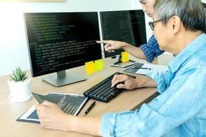 Senior Programmierer arbeitet mit Kollegen foto