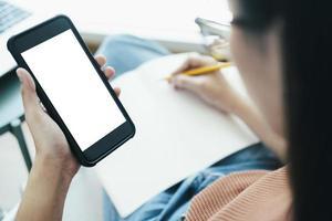 Nahaufnahme der Frauenhand, die Smartphone hält und ein Buch schreibt