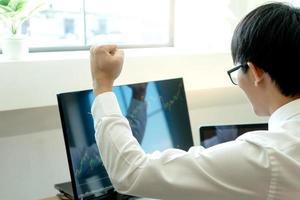 junger Geschäftsmann am Computer, der die Börse beobachtet foto
