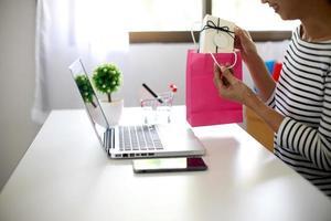 Frau sitzt an einem Computer und betrachtet ihren Kauf foto
