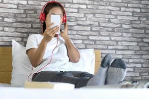 Frau, die sich auf dem Bett entspannt und Musik hört foto