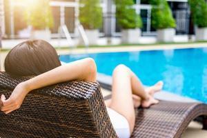 glückliche schöne Frau entspannendes Sonnenbad in der Nähe von Luxusschwimmbad foto