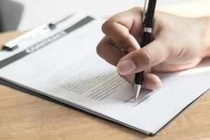 Nahaufnahme einer Person, die ein Dokument unterschreibt foto
