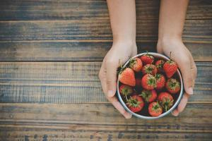 Draufsicht einer Person, die eine Schüssel Erdbeeren hält