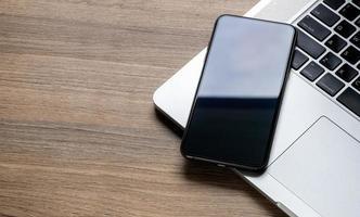 Nahaufnahme eines Smartphones auf einem Laptop