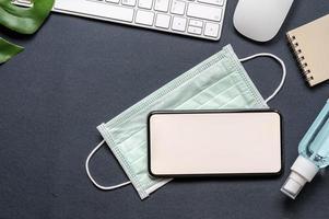 Smartphone-Modell auf einer Gesichtsmaske auf einem Schreibtisch