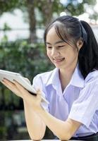 junger thailändischer Student mit Tablette