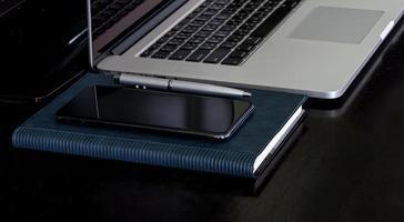 Laptop mit Smartphone und Notebook auf einem schwarzen Schreibtisch