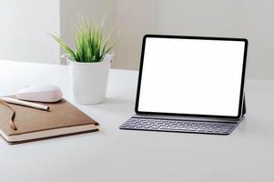 Tablette mit Tastaturmodell auf weißem Tisch