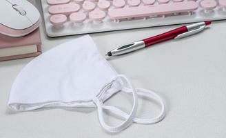 Gesichtsmaske auf einem Schreibtisch mit Tastatur und Stift foto