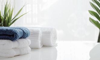 saubere Handtücher und Zimmerpflanzen auf einem weißen Tisch