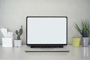 Laptop-Modell mit Pflanzen auf einem Schreibtisch foto
