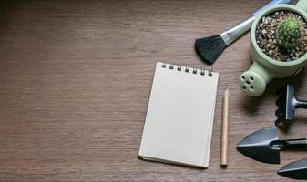 Draufsicht auf Gartengeräte und einen Notizblock