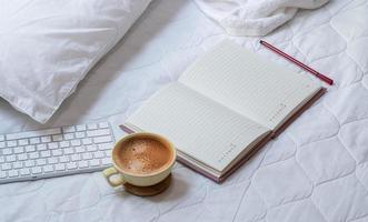 Kaffee mit einem Notizbuch und einer Tastatur auf einem Bett