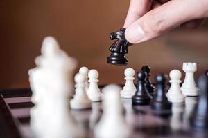 Hand bewegt einen Ritter auf einem Schachbrett