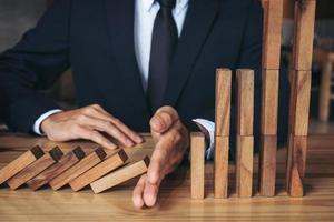 Nahaufnahme eines Geschäftsmannes, der verhindert, dass Holzblock fällt