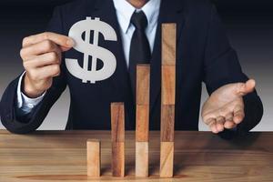 Geschäftsmann, der ein Dollarzeichen mit gestapelten Holzklötzen hält