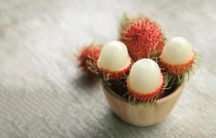 Rambutan in Holzschale schälen foto