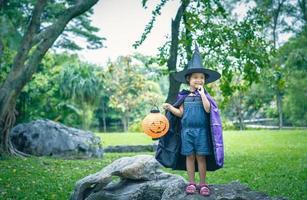 kleines Mädchen in einem Hexenkostüm, das eine Kürbislampe hält