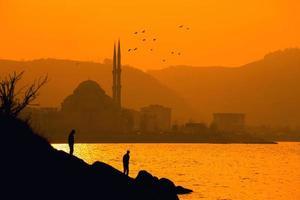 Silhouette von zwei Personen in der Nähe des Meeres foto