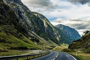graue Asphaltstraße zwischen Bergen foto