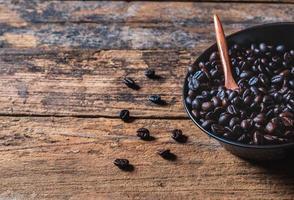 roher Kaffee in einer Pfanne auf Holztisch geröstet