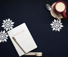 Kaffee und Notizbuch mit Schneeflocken auf einem dunklen Hintergrund