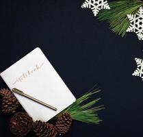 Notizbuch und Stift mit Tannenzapfen und Schneeflocken