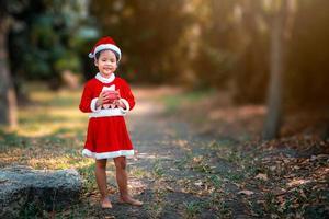 Mädchen, das ein Weihnachtsoutfit in einem Park trägt foto